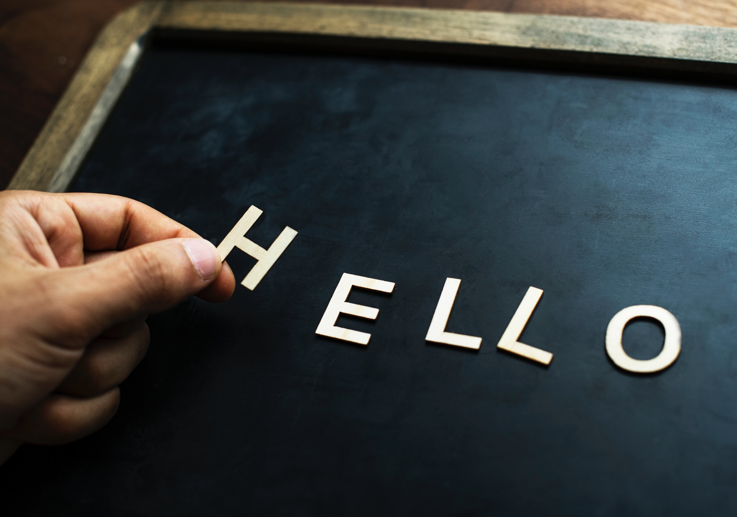 "black word board with wooden frame and white letters that spell ""hello"""