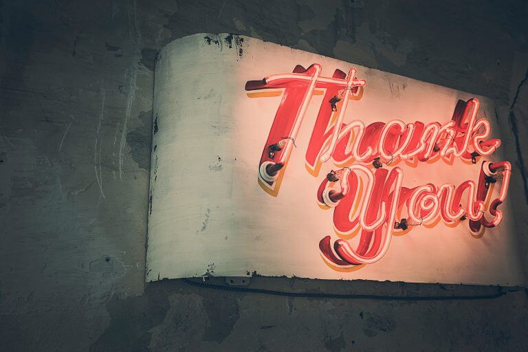 "close up shot of a worn cement sign on a wall with an illuminated red sign that says ""Thank You"" in cursive"