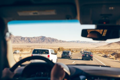 back seat passenger in a car looking out at the road and scenic dessert views with blue sky