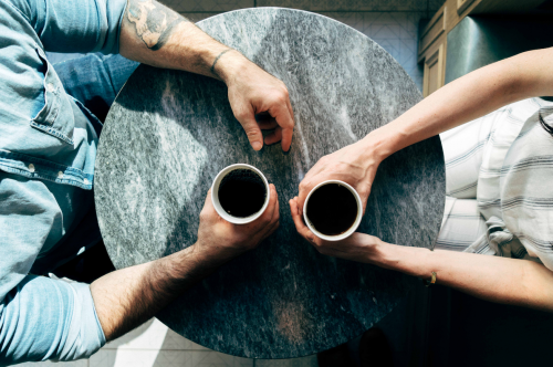 aerial image of a couple sitting at a small round metal table with two cups of coffee