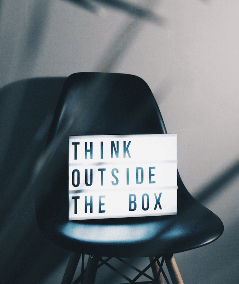 """black plastic chair with a sign that says """"think outside the box"""""""