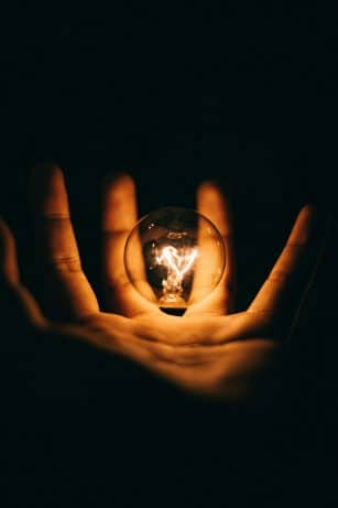 hand in a dark room with a light bulb lit up
