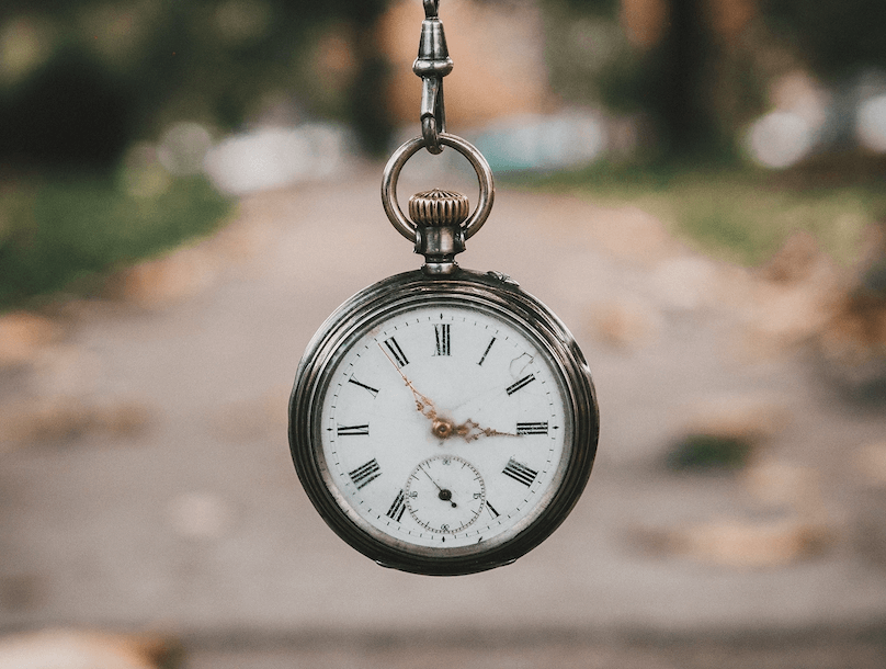 dated pocket watch hanging with a sidewalk blurred in the background