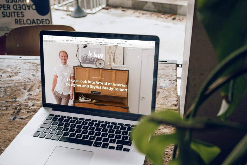 "mac laptop open to a the website ""le buzz"" near a plant in the corner of the shot"