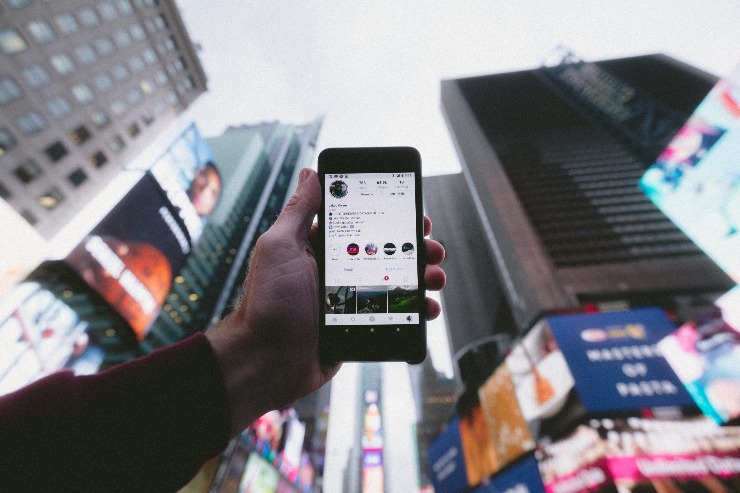 person holding cellphone up towards buildings in new york