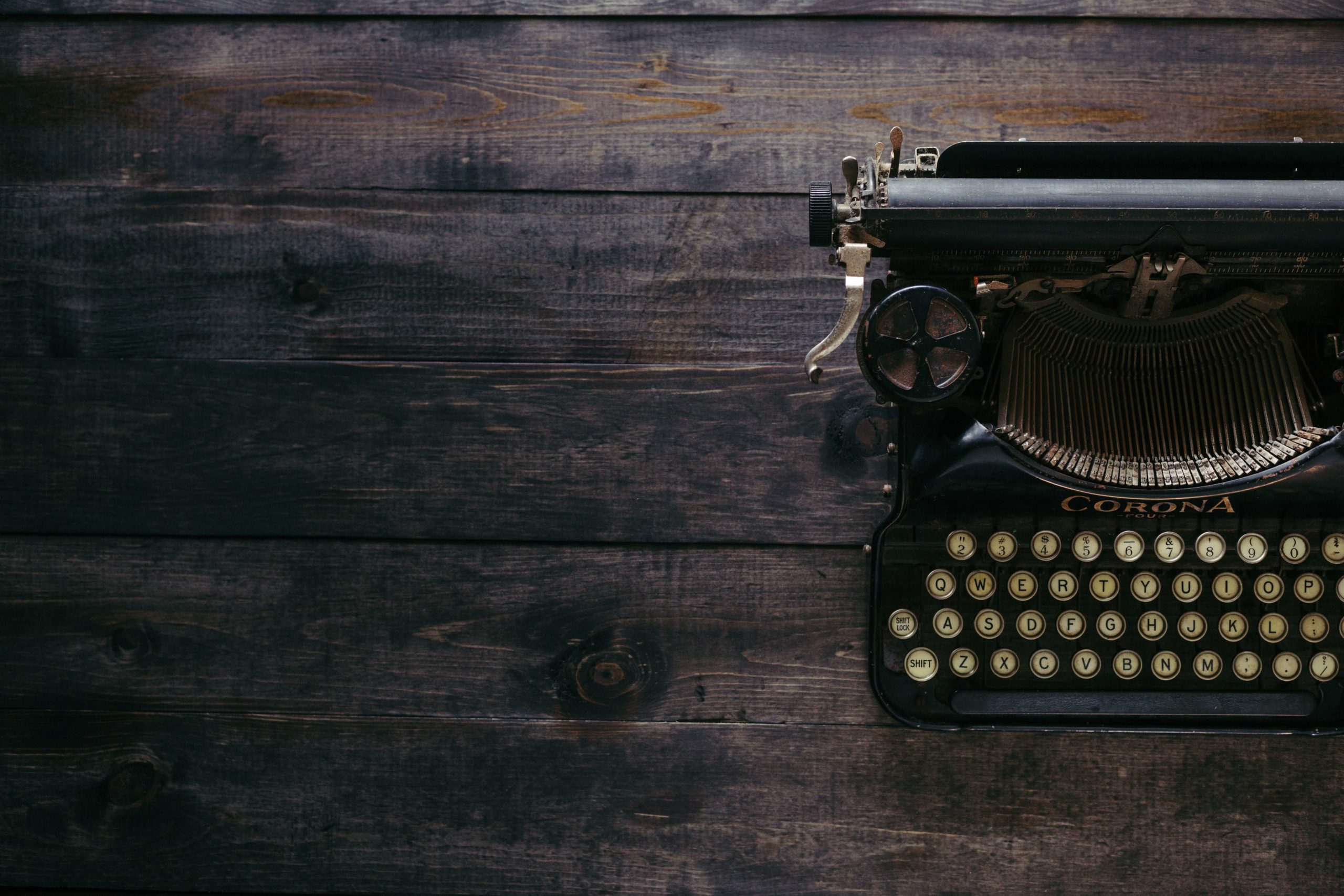 black typewriter on a wooden table