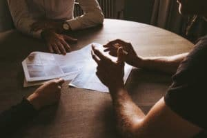 three people in a meeting at a round table with papers in the middle